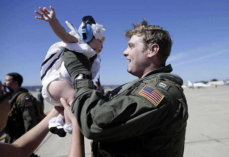 """Navy Lt. Gregory Campbell, of the Helicopter Sea Combat Squadron 23 """"Wildcards,"""" meets his daughter Bernadette for the first time as he arrives to Naval Air Station North Island after a seven-month deployment, Tuesday, Feb. 24, 2015, in San Diego. Nearly 4,500 Sailors and Marines with the Makin Island Amphibious Ready Group and the 11th Marine Expeditionary Unit are making their way home this week. (AP Photo/Gregory Bull)"""