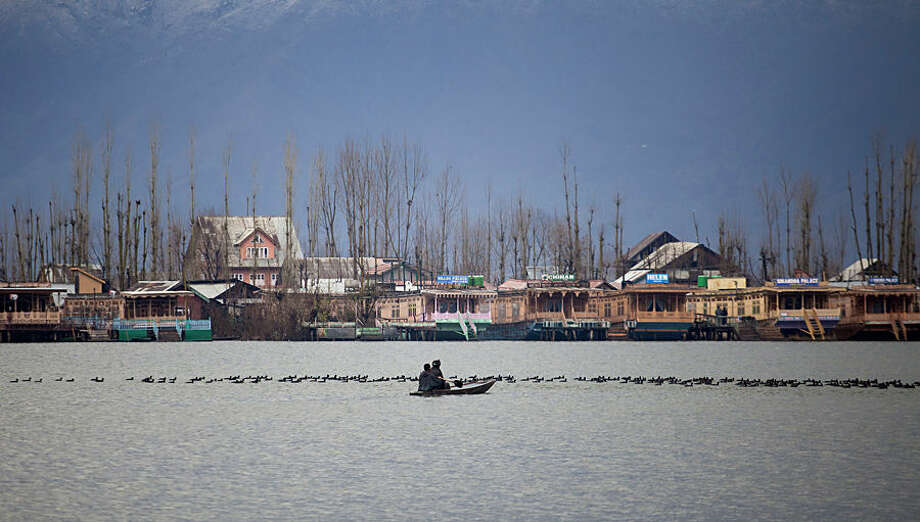 Kashmiri Muslims cross the Dal Lake on a small boat as migratory birds move on the water surface in Srinagar, India, Wednesday, Feb. 25, 2015. Kashmir experienced fresh snowfall with intermittent rains in other parts of the valley suspending vehicular movement on the 300 kilometers (186 miles) long Jammu-Srinagar national highway. (AP Photo/Dar Yasin)