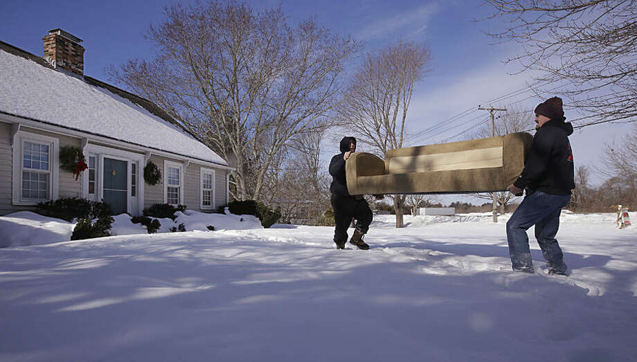 Encumbered by the snow pack, Kevin Thompson, right, and Dave Garro of Bold Moves Real Estate carry a couch used in staging the property for sale out of the front door and across the front yard, Tuesday, Feb. 24, 2015 in Mattapoisett, Mass. Real estate agents say purchase closings are being held up because of the heavy snow: Septic system inspectors can't find buried tanks, sellers can't easily have furniture delivered to stage a home for sale, and owners who do manage to sell a home are having a difficult time moving out. (AP Photo/Stephan Savoia)
