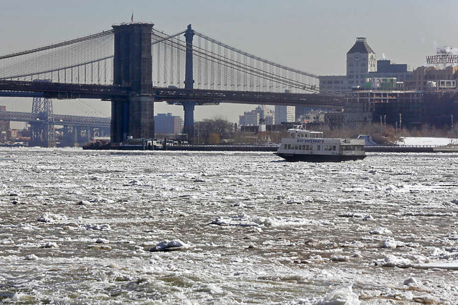 A New York Waterway ferry navigates through ice on the East River near the Brooklyn Bridge, Tuesday, Feb. 24, 2015, in New York. A wide swath of the country is experiencing record-breaking temperatures while other areas are expecting more winter precipitation Tuesday. (AP Photo/Richard Drew)