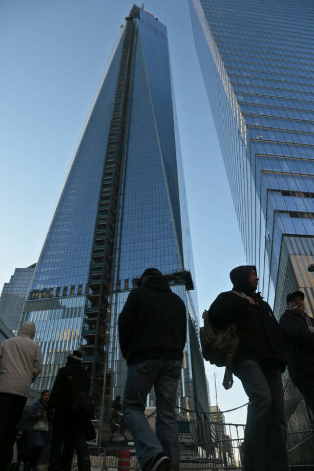 Pedestrians past a closed walkway next to the World Trade Center, left, on Tuesday Feb. 18, 2014 in New York. The new World Trade Center, the nation's tallest building, was recently cordoned off so pedestrians could avoid injury from falling ice. (AP Photo/Bebeto Matthews)