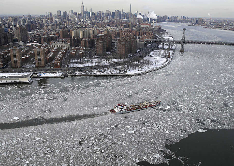 A boat makes its way through ice on the East River in New York, Tuesday, Feb. 24, 2015. A wide swath of the country is experiencing record-breaking temperatures while other areas are expecting more winter precipitation Tuesday. (AP Photo/Seth Wenig)