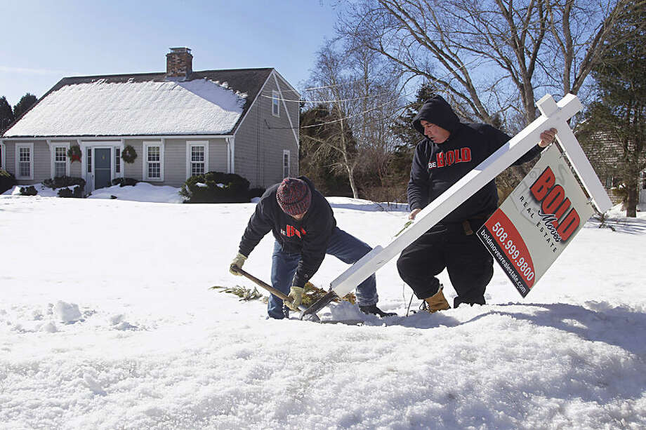 Kevin Thompson, left, and Dave Garro of Bold Moves Real Estate dig a real estate sign out of the snow pack in the front yard of a property on Crestfield Street after its sale, Tuesday, Feb. 24, 2015, in Mattapoisett, Mass. Real estate agents say purchase closings are being held up because of the heavy snow: Septic system inspectors can't find buried tanks, sellers can't easily have furniture delivered to stage a home for sale, and owners who do manage to sell a home are having a difficult time moving out. (AP Photo/Stephan Savoia)