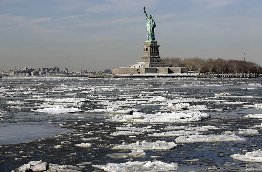Ice flows past the Statue of Liberty, Tuesday, Feb. 24, 2015, in New York. A wide swath of the country is experiencing record-breaking temperatures while other areas are expecting more winter precipitation Tuesday. (AP Photo/Richard Drew)