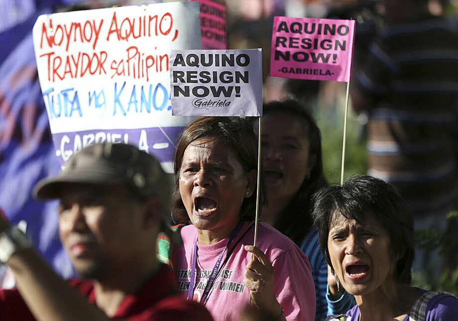 """Filipino women protesters shout slogans during a rally as part of their observance of the 29th anniversary of the People Power revolution in suburban Quezon city, north of Manila, Philippines, Wednesday, Feb. 25, 2015. The People Power revolt toppled the late dictator Ferdinand Marcos from 20-year-rule and helped install Corazon """"Cory"""" Aquino, the mother of President Benigno Aquino III, to the Presidency. The protesters were calling for the resignation of Aquino III for his alleged role in the botched police operation to capture Malaysian bomb-maker Zulkifli bin Hir also known as Marwan that resulted in the killings of 44 elite police commandos on Jan. 25. (AP Photo/Aaron Favila)"""