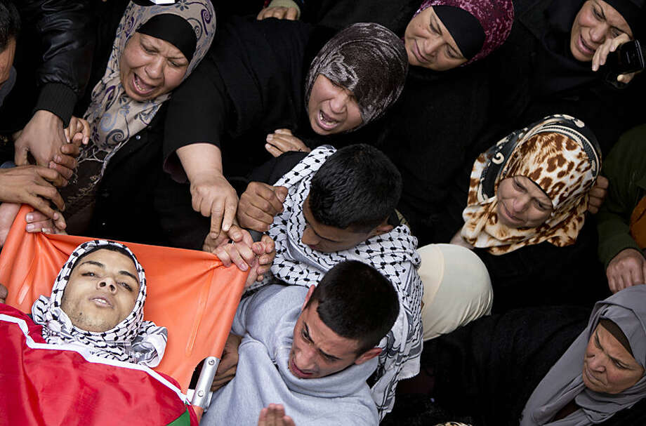 "Palestinian mourners carry the body of Jihad al-Jafari, 19, during his funeral in the Deheisha refugee camp near the West Bank city of Bethlehem, Tuesday, Feb. 24, 2015. Bethlehem Governor Jebren al-Bakri says al-Jafari was shot in the chest Tuesday morning on the roof of his house in the Deheisha refugee camp as he was watching a disturbance below. The Israeli military says troops on a ""routine activity"" were attacked with rocks and firebombs in the camp and feeling their lives were in danger, opened fire at one of the instigators. (AP Photo/Majdi Mohammed)"