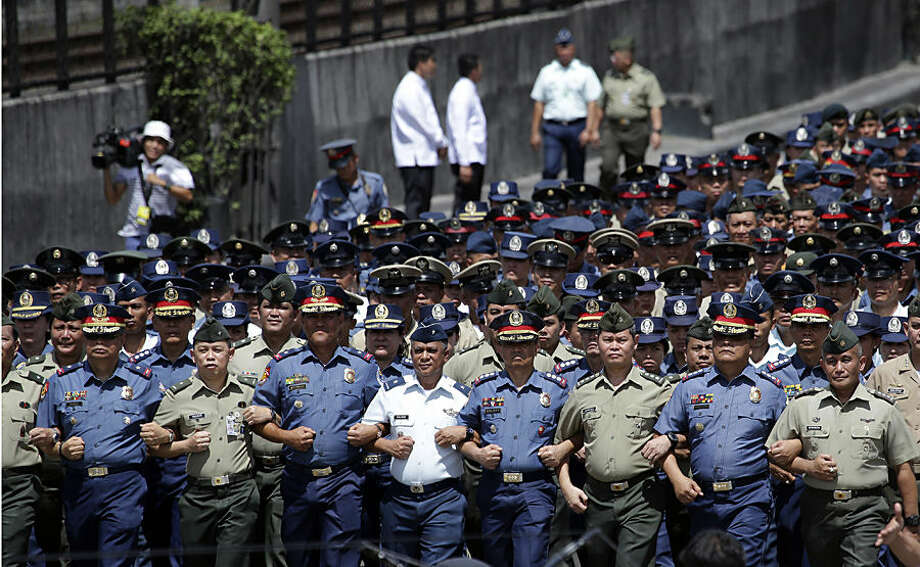 "Members of the Philippine police and Armed Forces of the Philippines link arms as they join the ""Unity Walk"" during the 29th anniversary celebration of the revolt known as People Power revolution at the People's Power Monument in suburban Quezon city, north of Manila, Philippines on Wednesday, Feb. 25, 2015. The People Power revolt toppled the late dictator Ferdinand Marcos from 20-year-rule and helped install Corazon ""Cory"" Aquino, the mother of President Benigno Aquino III, to the presidency. (AP Photo/Aaron Favila)"