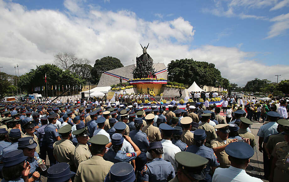 "Members of the Philippine police and Armed Forces of the Philippines join the 29th anniversary celebration of the revolt known as People Power revolution at the People's Power Monument in suburban Quezon city, north of Manila, Philippines on Wednesday, Feb. 25, 2015. The People Power revolt toppled the late dictator Ferdinand Marcos from 20-year-rule and helped install Corazon ""Cory"" Aquino, the mother of President Benigno Aquino III, to the presidency. (AP Photo/Aaron Favila)"