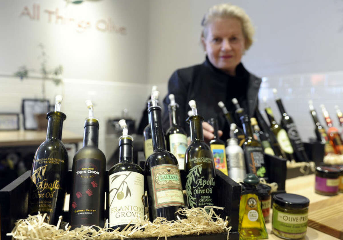 This photo taken Feb. 12, 2014 shows California Olive Oil Council Executive Director Patricia Darragh posing with a collection of California olive oil at the All Things Olive shop in Washington. It's a pressing matter for the tiny U.S olive oil industry.