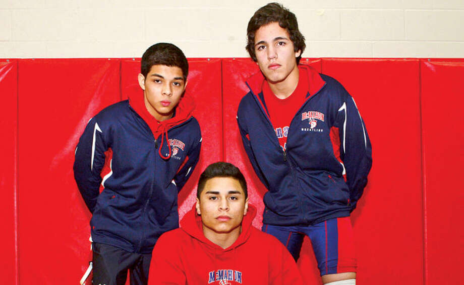 Hour photo / Erik Trautmann Jimmy Capone, his brother Jeff Capone, and their cousin Jason Martinez are all Brien McMahon High School wrestlers.