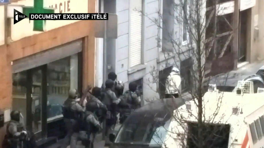 In this image taken from video made available on Monday March 21, 2016 a man believed to be Salah Abdeslam, right wearing white, the top suspect in the Paris attacks, runs from the police before being shot by the police during a raid in the Molenbeek neighborhood of Brussels, Belgium on Friday March 18, 2016. (I-Tele via AP) FRANCE OUT BELGIUM OUT TV OUT 24 HOURS USE ONLY NO ARCHIVE