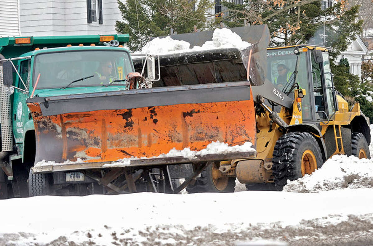 Hour photo / Erik Trautmann Norwalk DPW workers remove snow from East Avenue Wednesday.