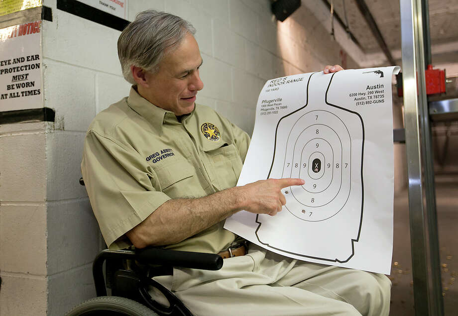 Texas Gov. Greg Abbott displays his marksmenship at Red's Indoor Range in Pfulgerville, Saturday, June 13, 2015. Abbott stopped at the gun range to sign into law bills letting Texans carry concealed handguns on college campuses and openly carry them virtually everywhere else. (Ralph Barrera /Austin American-Statesman via AP) Photo: Ralph Barrera, MBO / Austin American-Statesman
