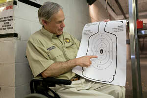 Texas Gov. Greg Abbott displays his marksmenship at Red's Indoor Range in Pfulgerville, Saturday, June 13, 2015. Abbott stopped at the gun range to sign into law bills letting Texans carry concealed handguns on college campuses and openly carry them virtually everywhere else. (Ralph Barrera /Austin American-Statesman via AP)