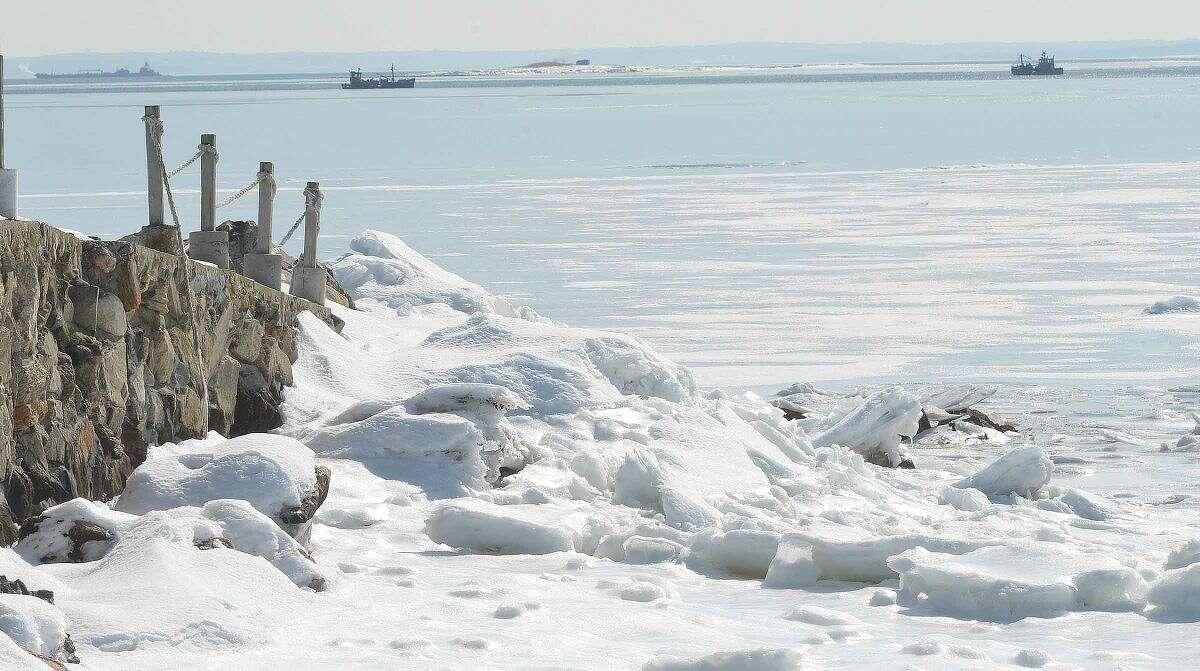 Hour Photo/Alex von Kleydorff Oyster boats in open water off the frozen shoreline in Westport