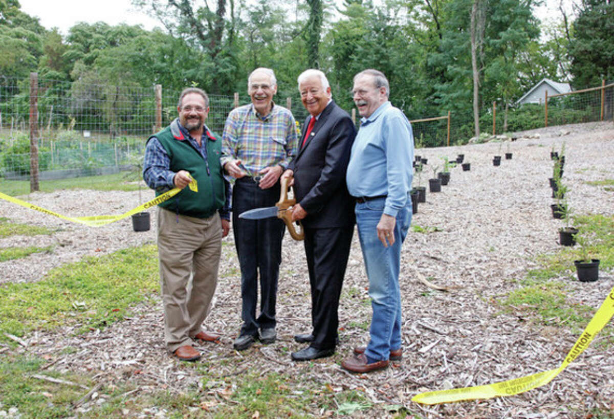 Hour photo / Danielle Calloway Michael Mocciae, Dan Landau, Mayor Moccia and Hal Alvord cut the ribbon during the Norwalk Tree Alliance's dedication of Fairfield County's first municipal tree farm incorporating a solar-powered irrigation system at Fodor Farm community garden in Norwalk Friday afternoon. A third-of-an-acre with fencing and a shed to store equipment has been allocated for the farm where native species trees are already being grown from saplings to be strategically planted on civic properties like parks and right-of-ways. An $8,000 America the Beautiful grant from the Connecticut Department of Energy and Environmental Protection--intended for urban forestry activities driven by nonprofits like the Norwalk Tree Alliance--initially funded the farm.