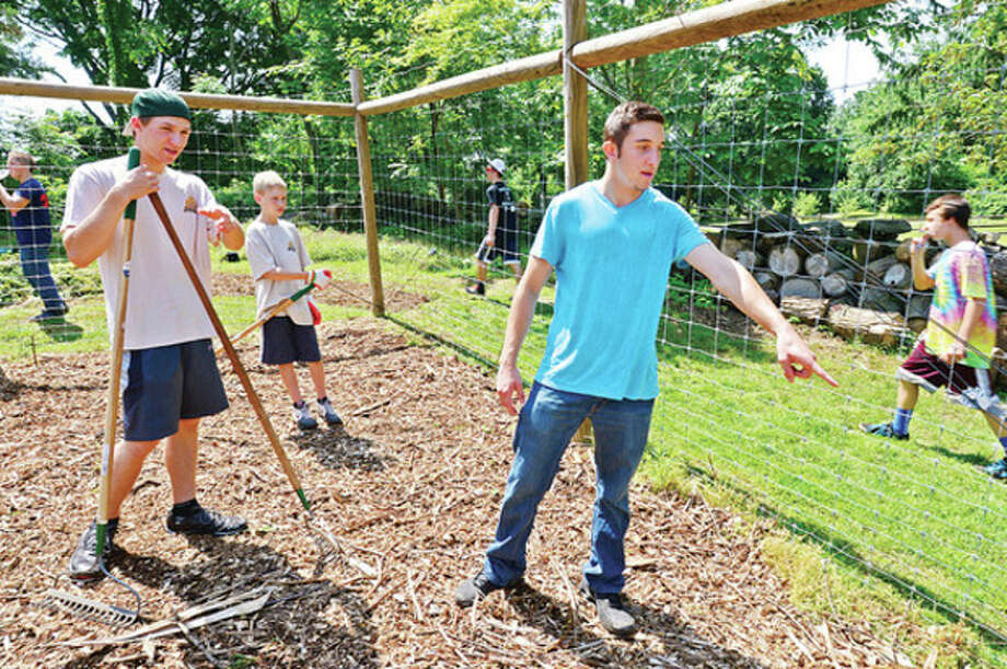 Hour photo / Erik TrautmannCommunity serviceDavid Rodriguez, right, directs his his crew of Scouts from Troop 2 in his community service project to finish the Tree Alliance Tree Farm at Fodor Farm Park in Norwalk Saturday to obtain his Eagle Scout badge. The Scouts painted a tool shed, spread mulch, and dug an irrigation trench. Requirements for Eagle Scout include earning at least 21 merit badges and demonstrating Scout Spirit through the Boy Scout Oath and Law, service, and leadership as well as an extensive service project that the Scout plans, organizes, leads, and manages. / (C)2013, The Hour Newspapers, all rights reserved