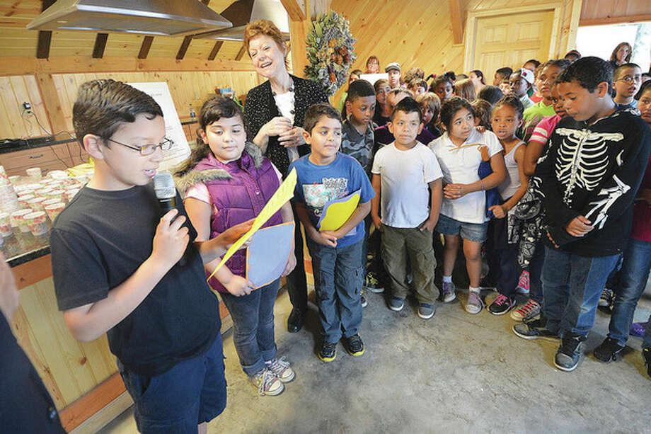 "Hour photo / Alex von KleydorffBrookside School third-grader Ramses Perez reads his poem ""Shasta Daisy"" during a reception at Fodor Farm for the installation of their sculptures."