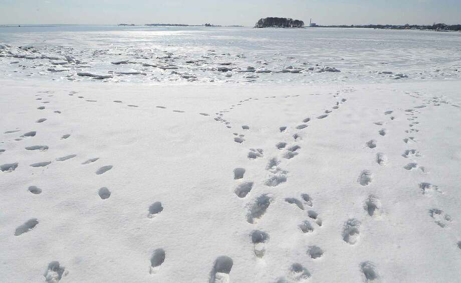 Hour Photo/Alex von Kleydorff Footprints lead head over snow and ice to more snow and ice at Canal Beach in Westport on Wednesday.