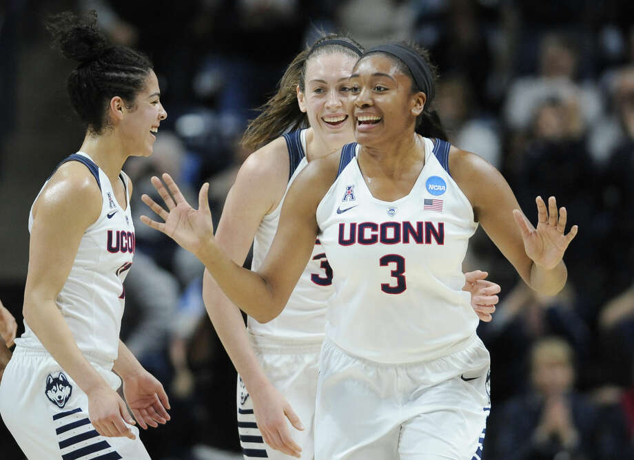 Connecticut's Morgan Tuck, right, celebrates with Kia Nurse, left, and Breanna Stewart, rear, after sinking a basket during the first half of a second round women's college basketball game against Duquesne in the NCAA Tournament, Monday, March 21, 2016, in Storrs, Conn. (AP Photo/Jessica Hill)