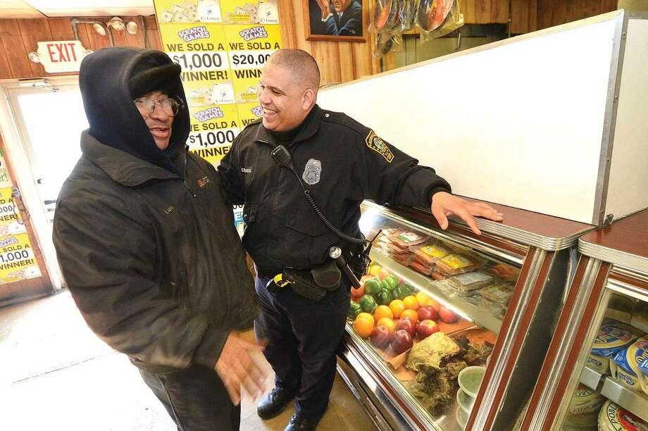 Hour Photo/Alex von Kleydorff Norwalk Police Officer Hector Delgado talks with freinds at C&S Grocery in his old neighborhood