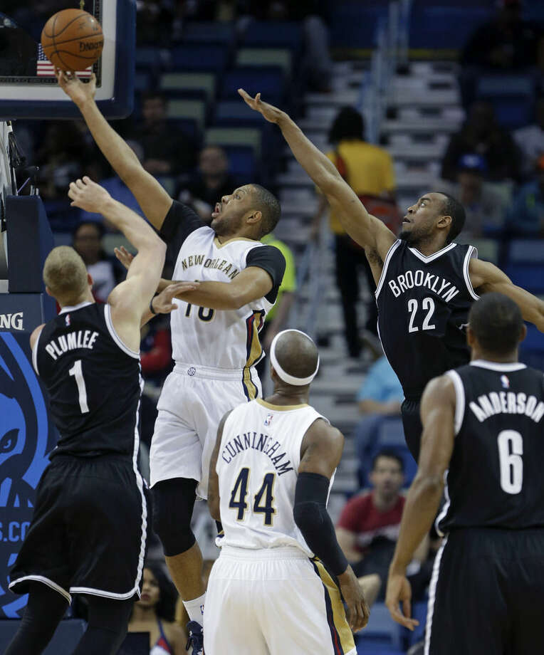 New Orleans Pelicans guard Eric Gordon (10) shoots between Brooklyn Nets center Mason Plumlee (1) and guard Markel Brown (22) in the first half of an NBA basketball game in New Orleans, Wednesday, Feb. 25, 2015. (AP Photo/Gerald Herbert)