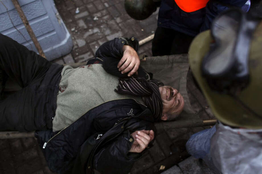 An injured anti-government protester is carried away to get treatment on the outskirts of Independence Square in Kiev, Ukraine, Thursday, Feb. 20, 2014. Fierce clashes between police and protesters, some including gunfire, shattered a brief truce in Ukraine's besieged capital Thursday, killing numerous people. The deaths came in a new eruption of violence just hours after the country's embattled president and the opposition leaders demanding his resignation called for a truce and negotiations to try to resolve Ukraine's political crisis. (AP Photo/Marko Drobnjakovic)