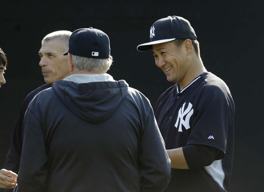 New York Yankees starting pitcher Masahiro Tanaka, of Japan, right, talks with manager Joe Girardi, left, and pitching coach Larry Rothschild, center, after throwing in the bullpen during a spring training baseball workout, Thursday, Feb. 26, 2015, in Tampa, Fla. (AP Photo/Lynne Sladky)