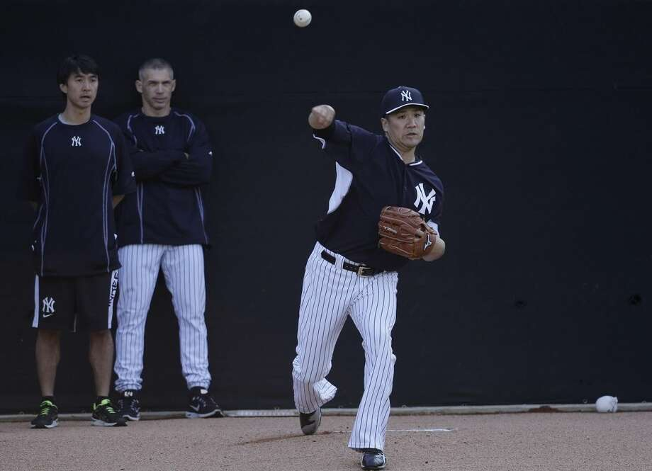 New York Yankees starting pitcher Masahiro Tanaka, of Japan, right, throws in the bullpen as manager Joe Girardi, center, look on during a spring training baseball workout, Thursday, Feb. 26, 2015, in Tampa, Fla. (AP Photo/Lynne Sladky)
