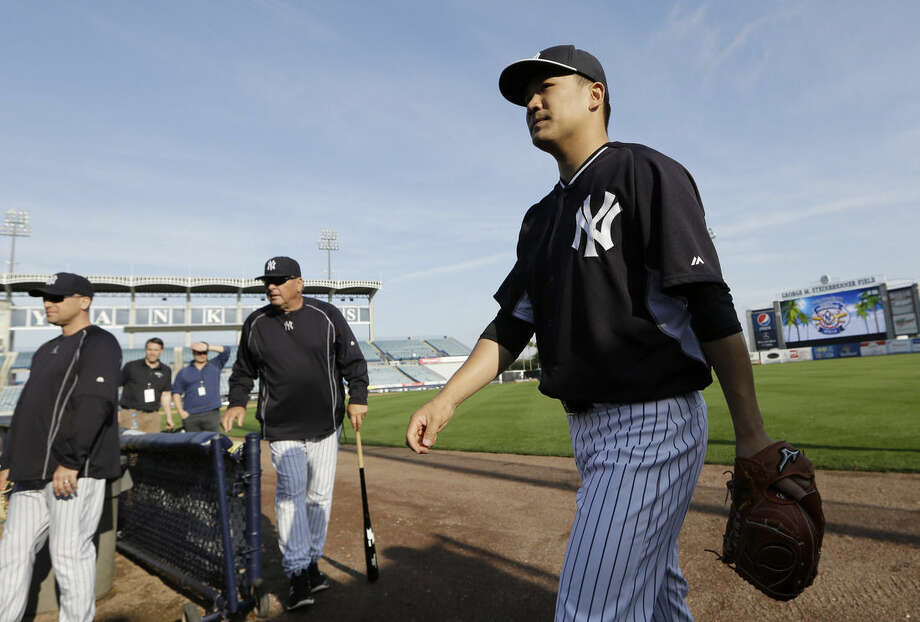 New York Yankees starting pitcher Masahiro Tanaka, of Japan, right, walks off the field to throw in the bullpen during a spring training baseball workout, Thursday, Feb. 26, 2015, in Tampa, Fla. (AP Photo/Lynne Sladky)