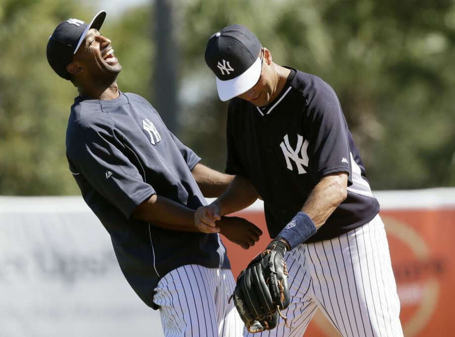 New York Yankees shortstop Eduardo Nunez, left, laughs with teammate shortstop Derek Jeter during spring training baseball practice Thursday, Feb. 20, 2014, in Tampa, Fla. (AP Photo/Charlie Neibergall)
