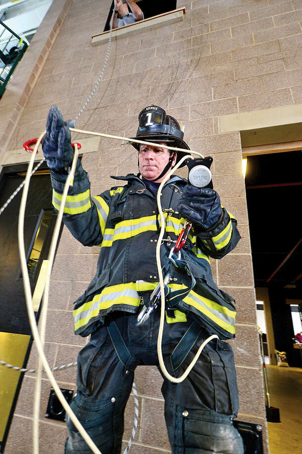 Hour photo / Erik Trautmann Norwalk firefighters including Mike Fratello train at the Norwalk Central Station on the Deus Personal Escape System that allows firefighters escape deadly situations by exiting quickly from the upper stories of buildings.