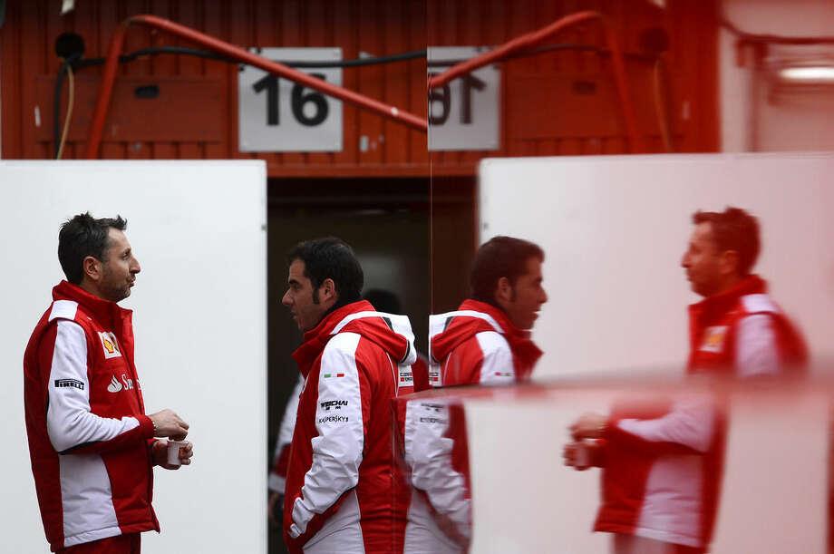 Ferrari mechanics talk in the paddock, during the 2015 Formula One testing at the Barcelona Catalunya racetrack, in Montmelo, Spain, Thursday, Feb. 26, 2015. (AP Photo/Manu Fernandez)