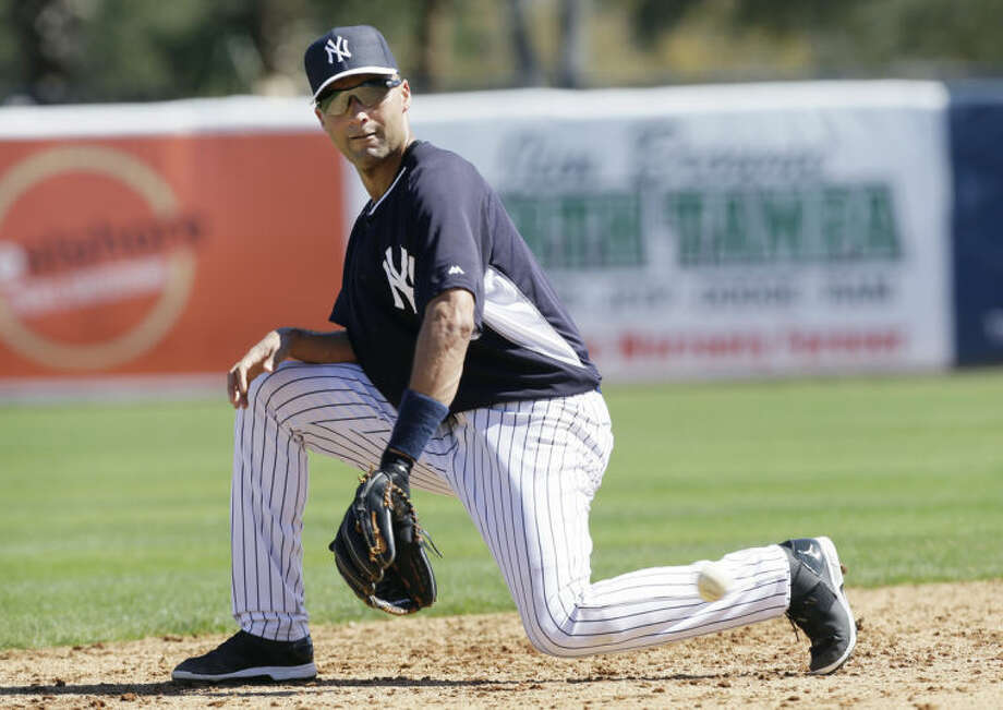 New York Yankees shortstop Derek Jeter fields a ground ball during spring training baseball practice Thursday, Feb. 20, 2014, in Tampa, Fla. (AP Photo/Charlie Neibergall)