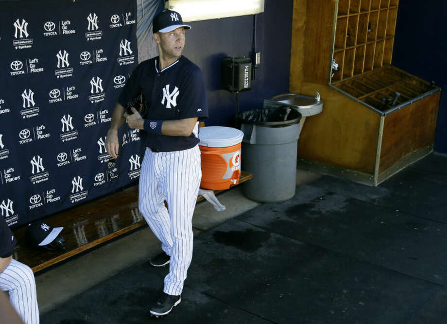 New York Yankees shortstop Derek Jeter walks in the dugout during spring training baseball practice Thursday, Feb. 20, 2014, in Tampa, Fla. (AP Photo/Charlie Neibergall)