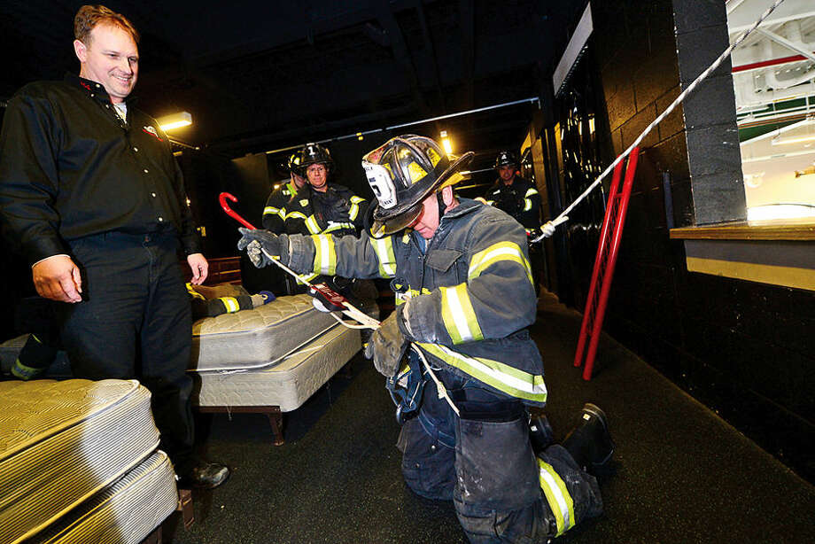 Hour photo / Erik Trautmann An instructor from the Fire Operations Group in Long Island help Norwalk firefighters including Lt. Adam Tyrrell train at the Norwalk Central Station on the Deus Personal Escape System that allows firefighters escape deadly situations by exiting quickly from the upper stories of buildings.