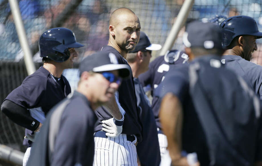 New York Yankees shortstop Derek Jeter, center, waits to hit in the batting cage during spring training baseball practice Thursday, Feb. 20, 2014, in Tampa, Fla. (AP Photo/Charlie Neibergall)