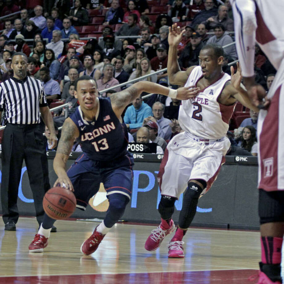 Connecticut's Shabzz Napier (13) drives against Temple's Will Cummings (2) in the first half of an NCAA college basketball game, Thursday, Feb. 20, 2014 in Philadelphia. (AP Photo/H. Rumph Jr.)