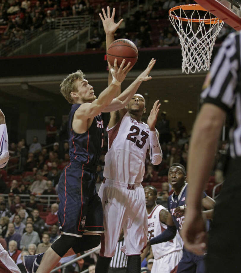 Connecticut's Niels Giffey, left shoots as Temple's Devontae Watson (23) defends in the first half of an NCAA college basketball game, Thursday, Feb. 20, 2014 in Philadelphia. (AP Photo/H. Rumph Jr.)