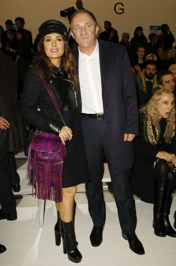 Mexican actress Salma Hayek, left, poses with her husband François-Henri Pinault, of France, prior to the start of the Gucci women's Fall-Winter 2014-15 collection, part of the Milan Fashion Week, unveiled in Milan, Italy, Wednesday, Feb. 19, 2014. (AP Photo/str)