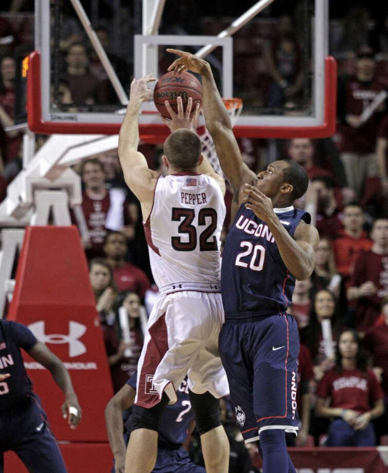 Connecticut's Lasan Kromah (20) blocks a shot by Temple's Dalton Pepper (32) in the first half of an NCAA college basketball game, Thursday, Feb. 20, 2014 in Philadelphia. (AP Photo/H. Rumph Jr.)