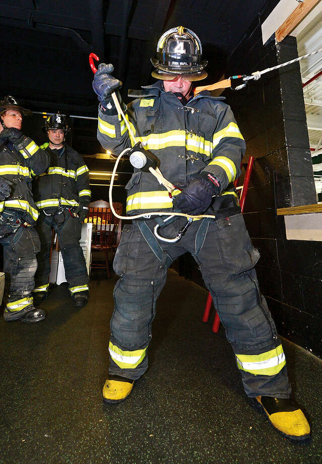 Hour photo / Erik Trautmann Norwalk firefighters including James Cocchia train at the Norwalk Central Station on the Deus Personal Escape System that allows firefighters escape deadly situations by exiting quickly from the upper stories of buildings.