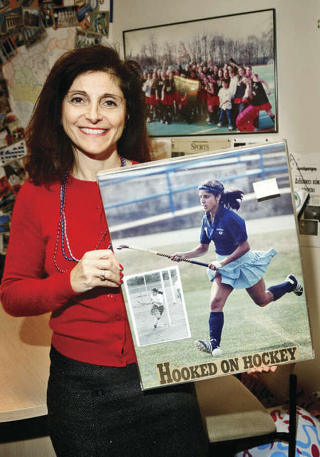 Hour photo/Erik TrautmannBrien McMahon Housemaster Mary Michailidis holds a picture of herself when she played field hockey at the University of North Carolina, and a smaller photo of when she starred at Westhill High School. On Saturday the former All-American will be in Philadelphia trying out for the USA Women's Masters Over-50 National Team with a chance to play in the World Cup in Holland.