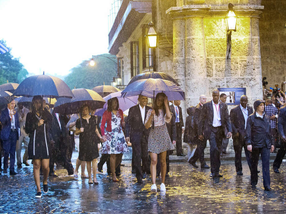 U.S. President Barack Obama, center, with his first lady Michelle Obama, daughters Malia and Sasha and first lady's mother Marian Robinson, take a walking tour of Old Havana in the rain, Sunday, March 20, 2016 in Havana, Cuba. Obama became the first U.S. president to visit the island in nearly 90 years. (AP Photo/Pablo Martinez Monsivais)