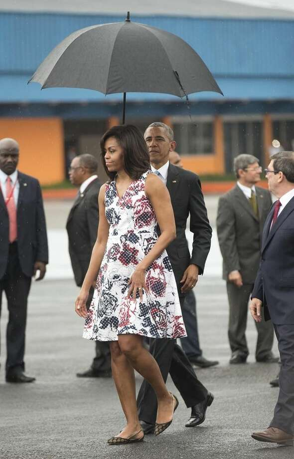 U.S. President Barack Obama holds an umbrella for first lady Michelle Obama as they walk across the tarmac upon their arrival at Jose Marti International Airport in Havana, Cuba. Sunday, March 20, 2016. Obama and his family traveled to Cuba Sunday, becoming the first U.S. president to visit the island in nearly 90 years. (AP Photo/Pablo Martinez Monsivais)