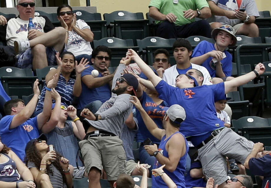Fans try to catch a foul ball in a spring training baseball game between the Atlanta Braves and the New York Mets, Saturday, March 26, 2016, in Kissimmee, Fla. (AP Photo/John Raoux)