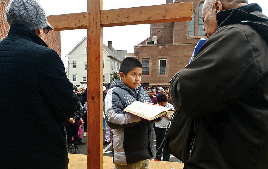 Hour photo / Erik Trautmann Christian Hernandez, 8, helps Father Frantz Desruisseaux read prayer as nearly 100 parishioners of St. Joseph's Church observe the Living Stations of the Cross at the church in South Norwalk on Good Friday.