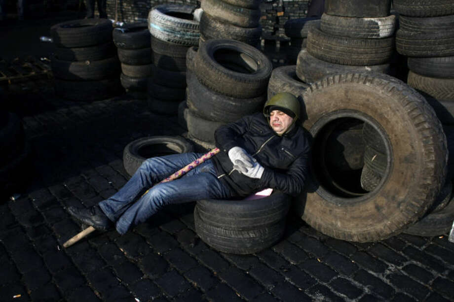 An anti-government protester catches some sleep on a barricade at Independence Square in Kiev, Ukraine, Friday, Feb. 21, 2014. Ukraine's presidency said Friday that it has negotiated a deal intended to end battles between police and protesters that have killed scores and injured hundreds, but European mediators involved in the talks wouldn't confirm a breakthrough. (AP Photo/ Marko Drobnjakovic)