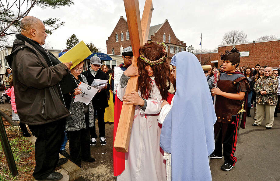 Hour photo / Erik Trautmann Father Frantz Desruisseaux reads prayer as Darwin Aplacano and Alexandra Garcia portray Jesus and Mary while nearly 100 parishioners of St. Joseph Church observe the Living Stations of the Cross at the church in South Norwalk on Good Friday.