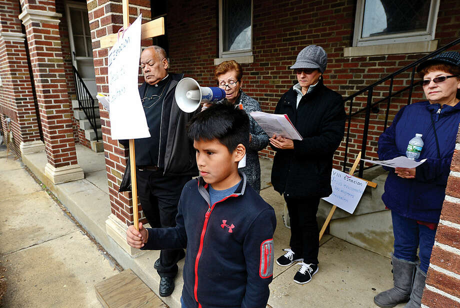 Hour photo / Erik Trautmann Octavio Pena, 9, marks the final station as nearly 100 parishioners of St. Joseph Church observe the Living Stations of the Cross at the church in South Norwalk on Good Friday.